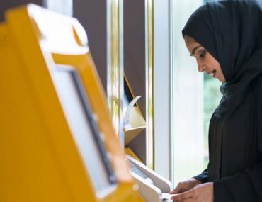 A girl is withdrawing money from ATM