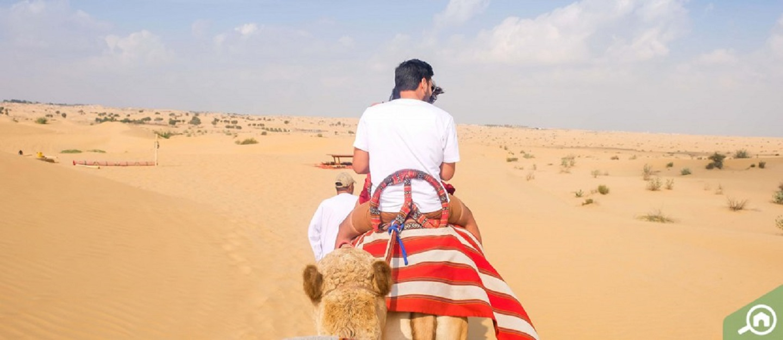 Man camel riding during desert safari in Dubai