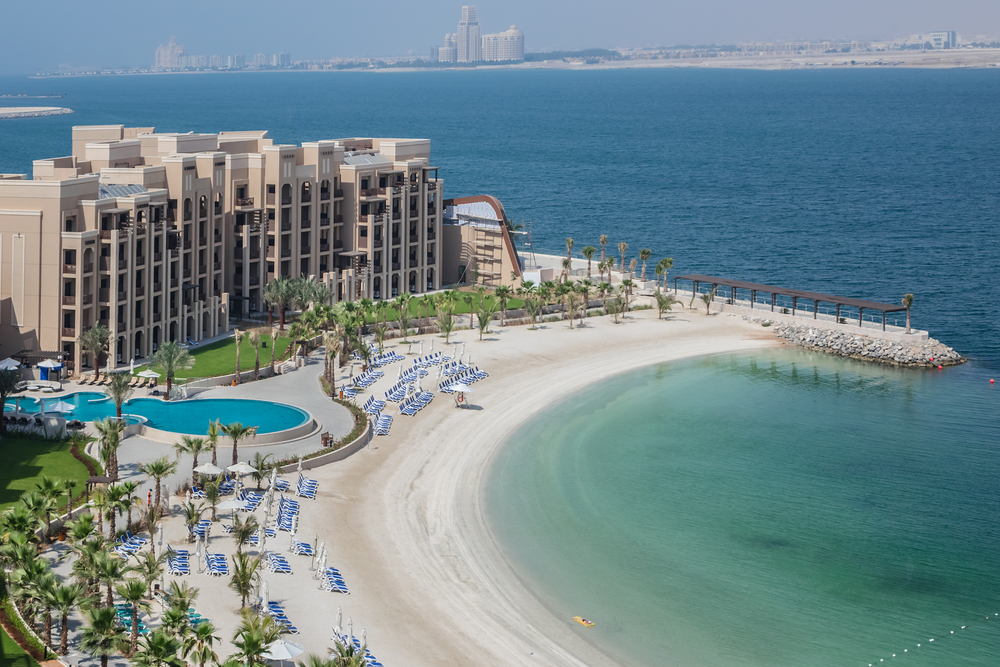 A wide shot of the DoubleTree by Hilton hotel in RAK with the white sandy beach and the crystal-blue waters of the Arabian Gulf