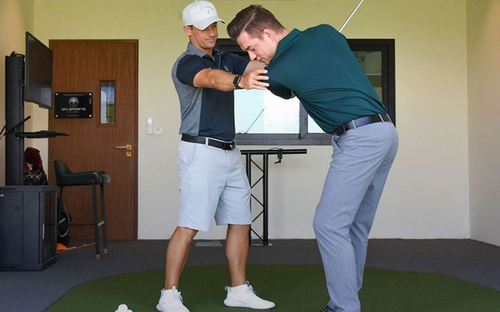 A trainer is correcting the shot angle of a golfer.  (Image credits: Dubai Hills Golf Club Facebook Page)