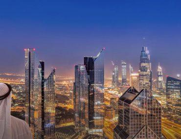 An Arab businessman looks at the skyline of Dubai