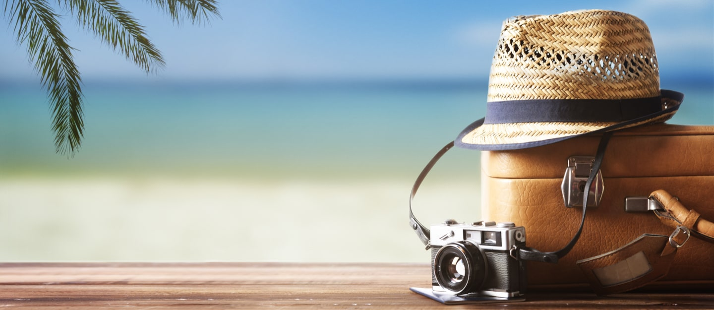 image showing a sun hat, travel case and camera against a beach background
