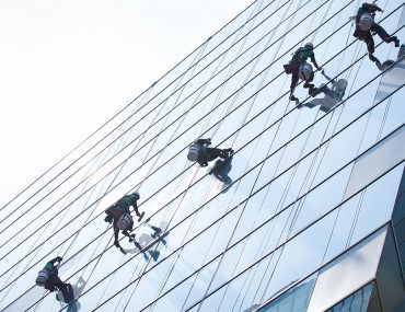 People cleaning windows of high rise, one of the services by facility management companies in Dubai