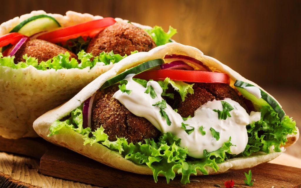 Plate of falafel sandwich with vegetable filling