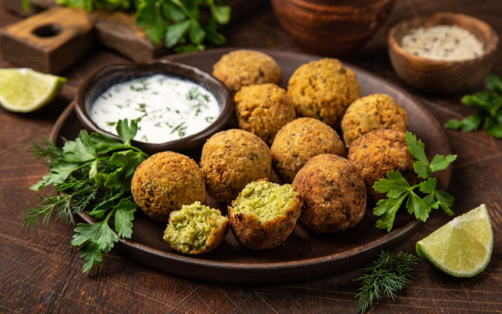 Plate of falafel with a side of sauce.