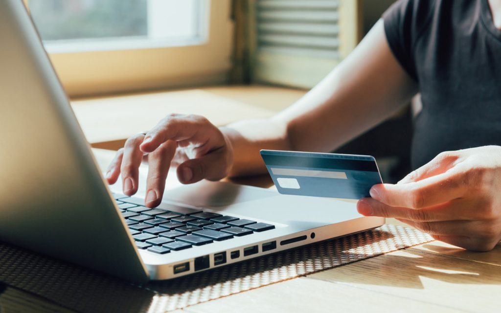 Person on laptop holding a credit card