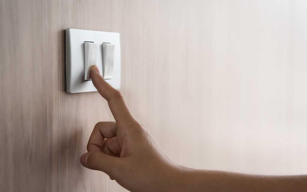 Hand on a light switch