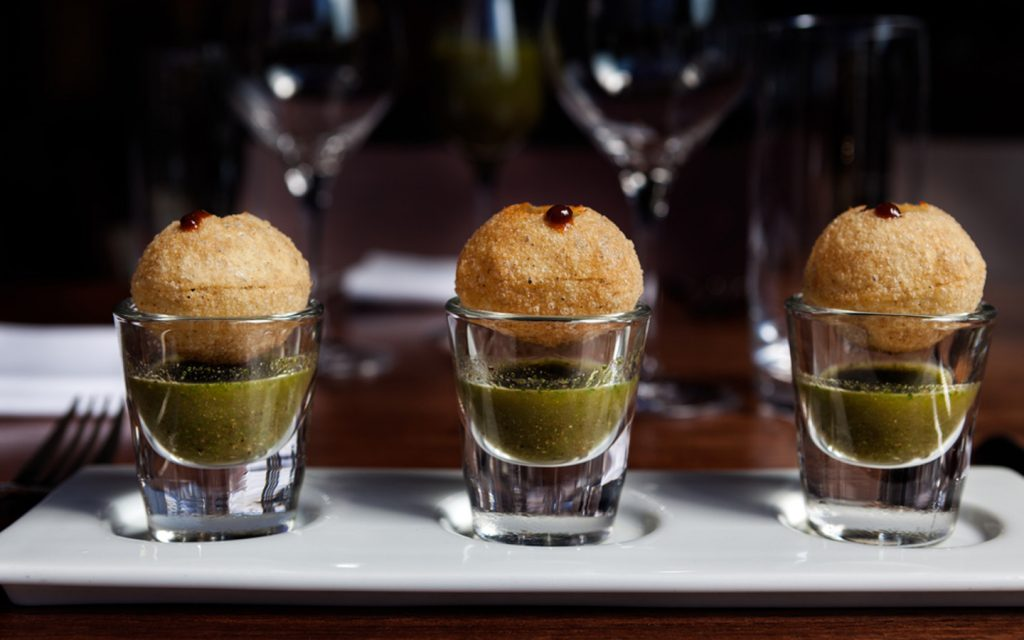 Pani Puris with sauce placed in shot glasses at fine dining Indian restaurants in Abu Dhabi