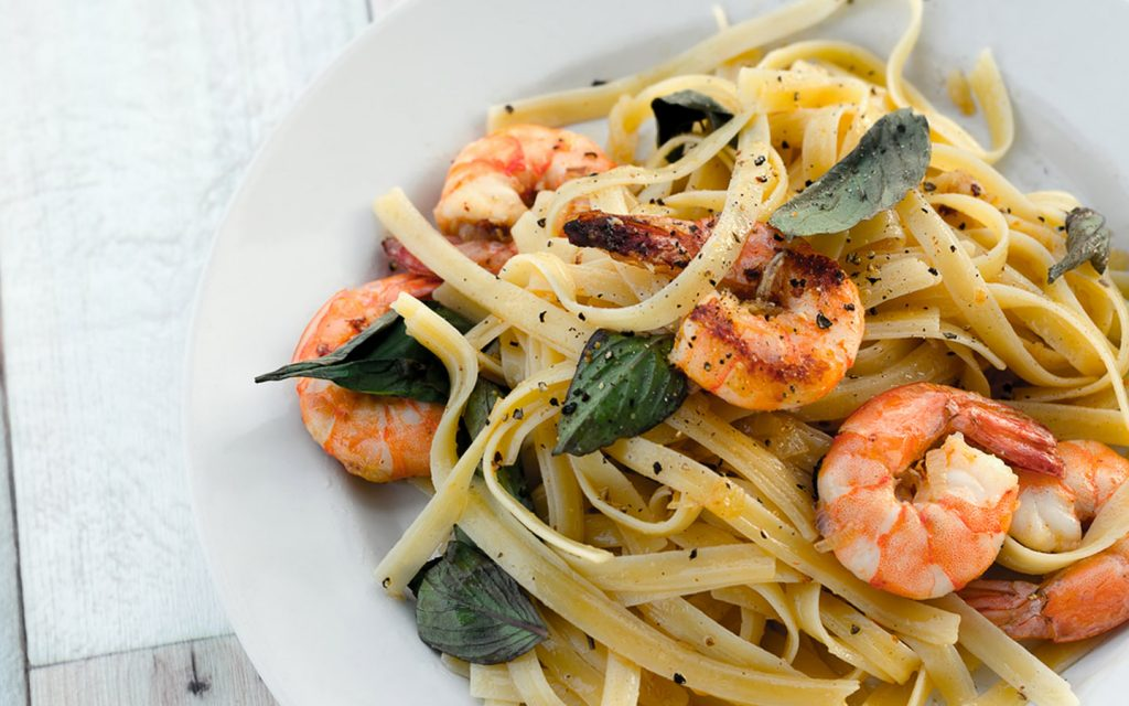 Pasta with grilled prawns served with herbs and black pepper