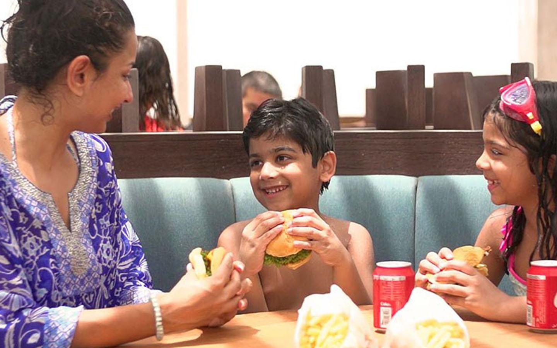 ام واطفالها يناولون وجبة في المطعم