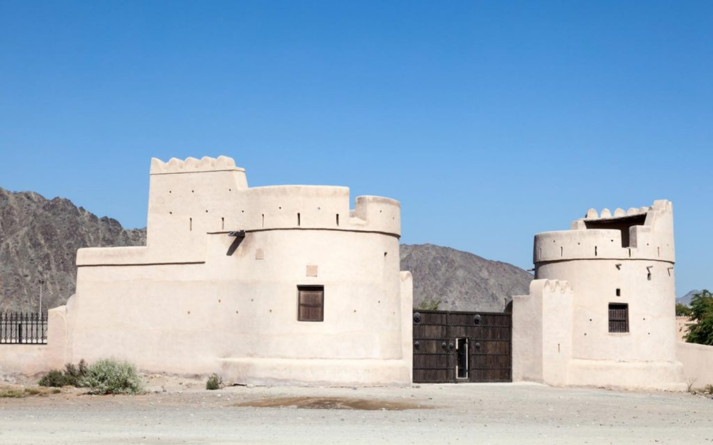 A house in Fujairah Heritage Village with mountains in the background