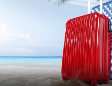 Suitcases on the beach for the best cheap getaways from Dubai