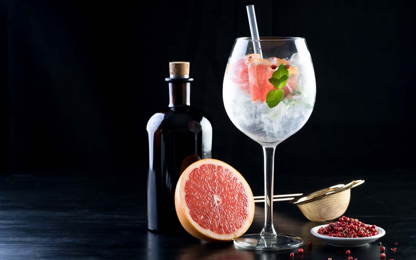 Gin and tonic with a blood orange and wine bottle