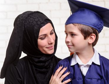Mom in an abaya and son in a graduation gown