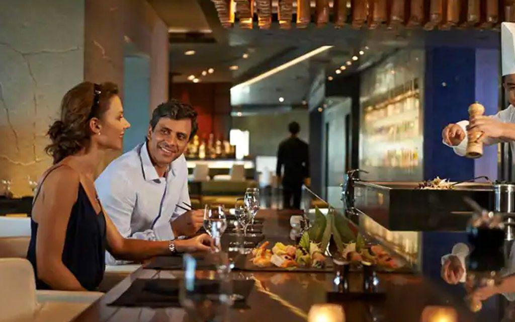 Couple dining at a fine dining restaurant at Waldorf Astoria Resort in RAK