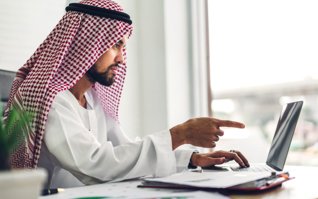 A man looking at the guide for renting in Dubai on his laptop