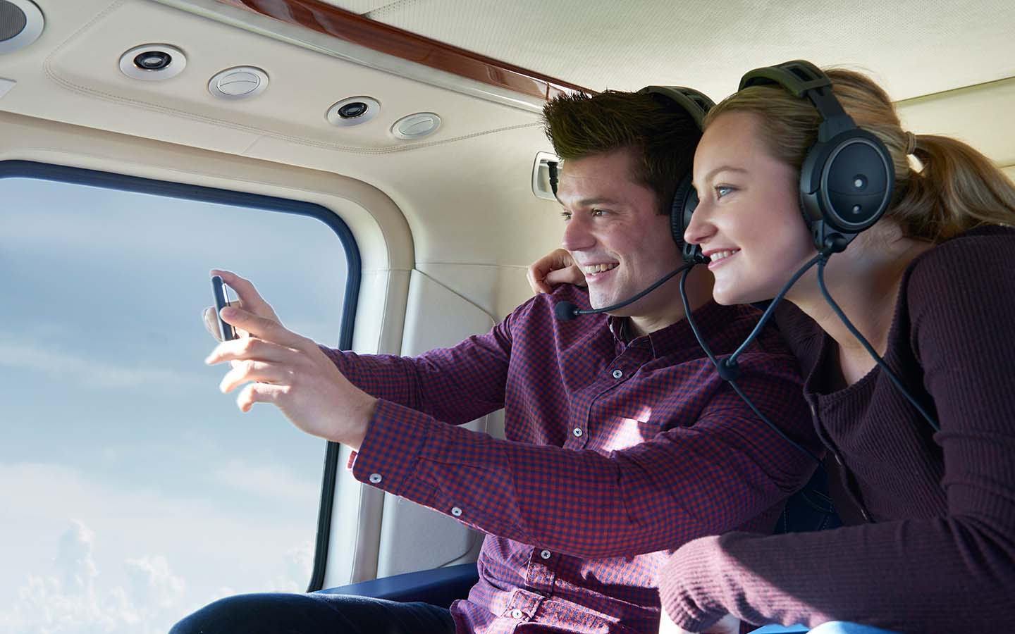 A couple take a picture from a helicopter
