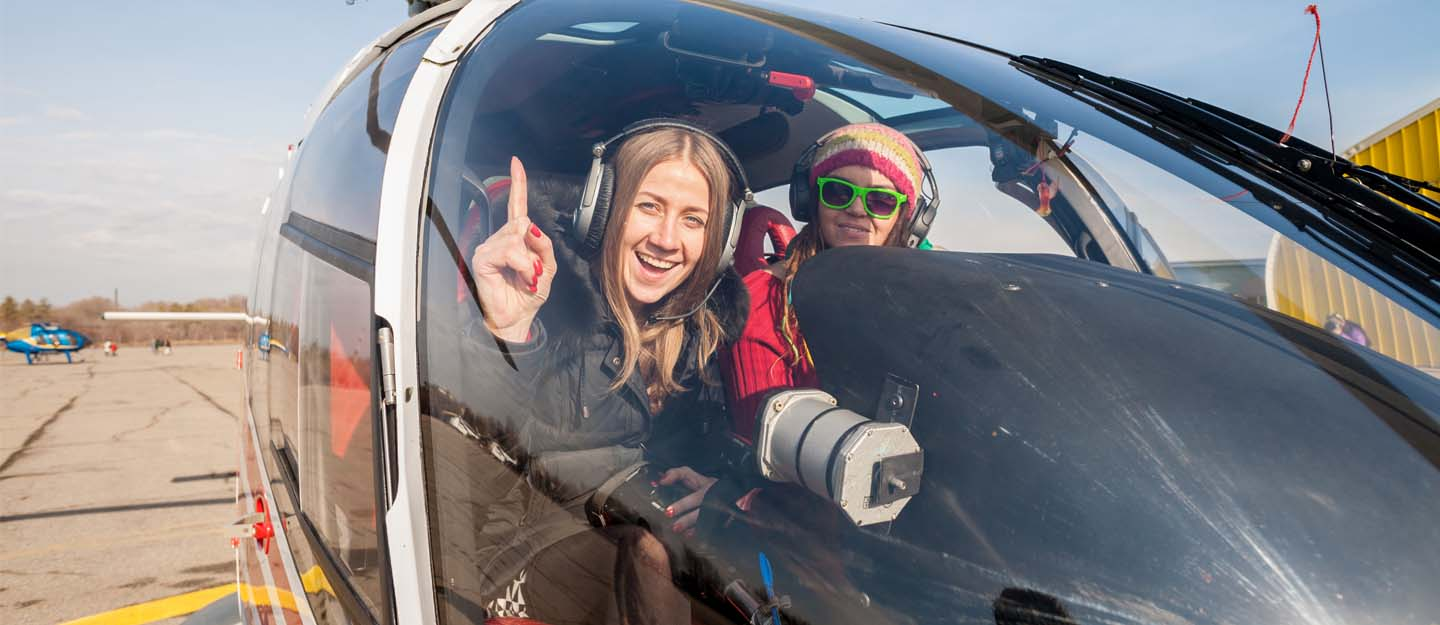 Two girls in a helicopter ready for Atlantis Helicopter Tour