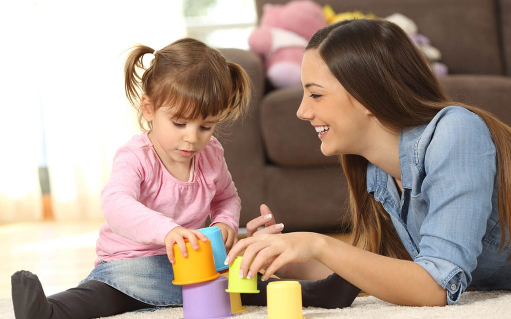 Woman sitting with a small girl, providing part time nanny services in Abu Dhabi