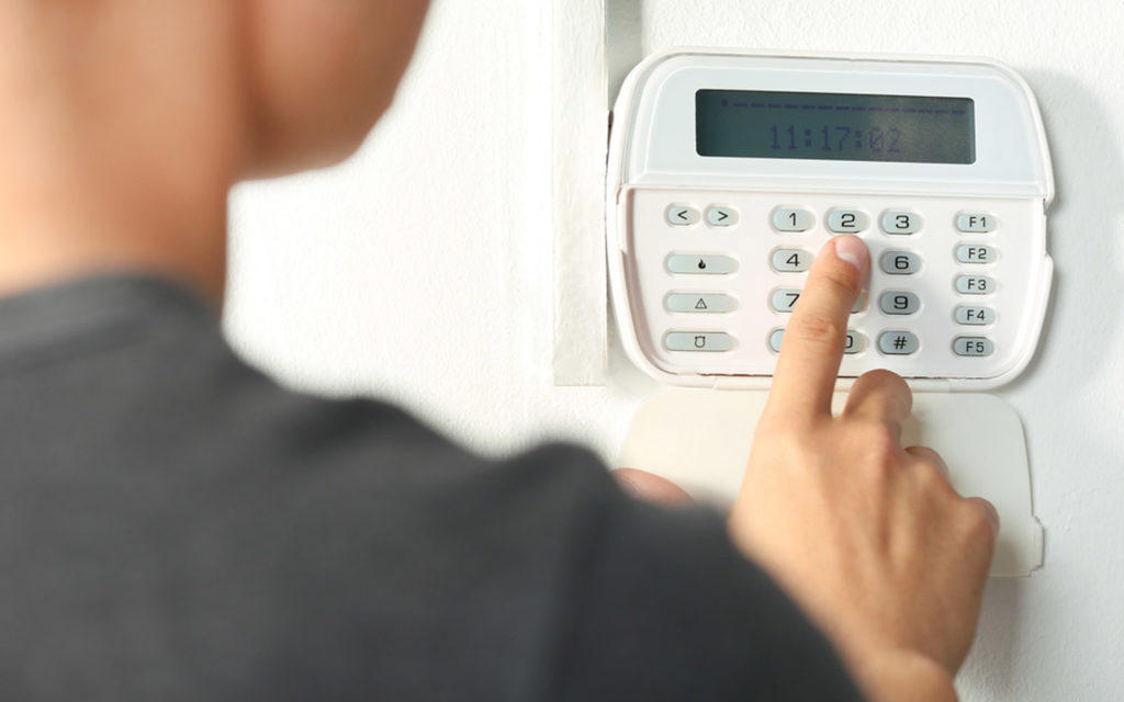 Man entering code in burglar alarm