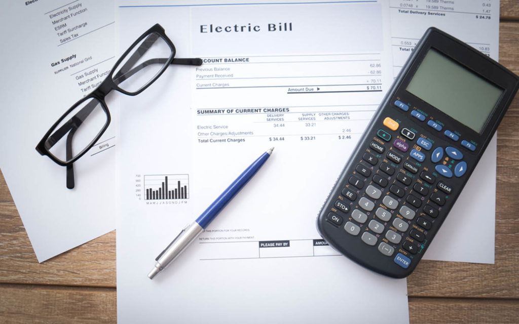 Utility bill with calculator and glasses