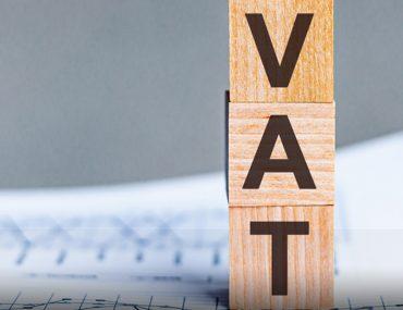 Wooden blocks spelling VAT placed on business document