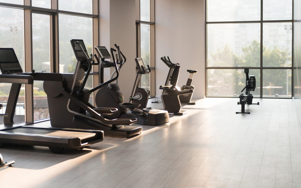 A home gym lighted naturally through floor to ceiling windows
