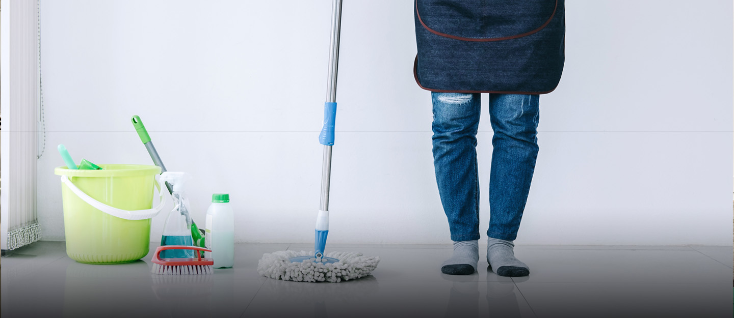 woman standing with cleaning supplies