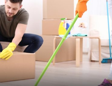 Woman cleaning home while man handles box while wearing gloves during home move