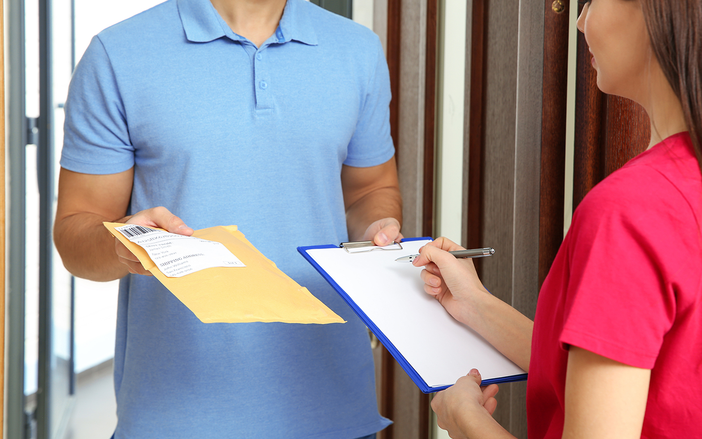 Woman receiving a package from a courier service