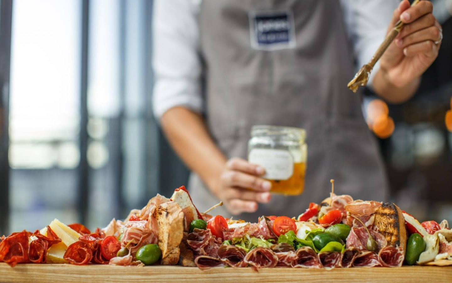 Image of different cuts of meat and vegetables with a chef in the background