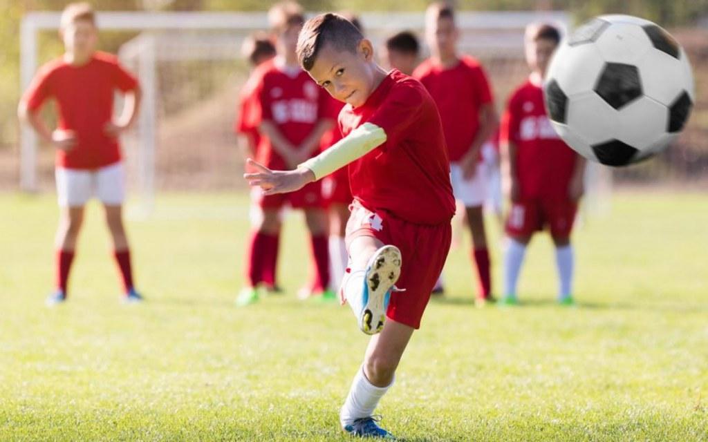 طفل يلعب كرة القدم