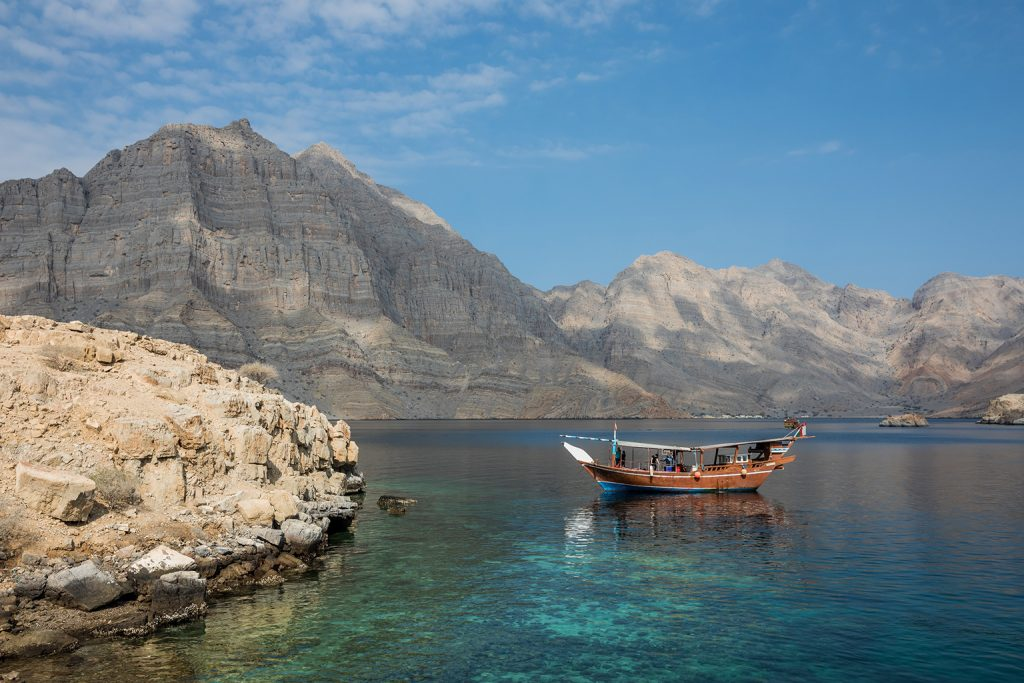 An Omani tourist boat on crystal-blue waters underneath a beautiful mountainside