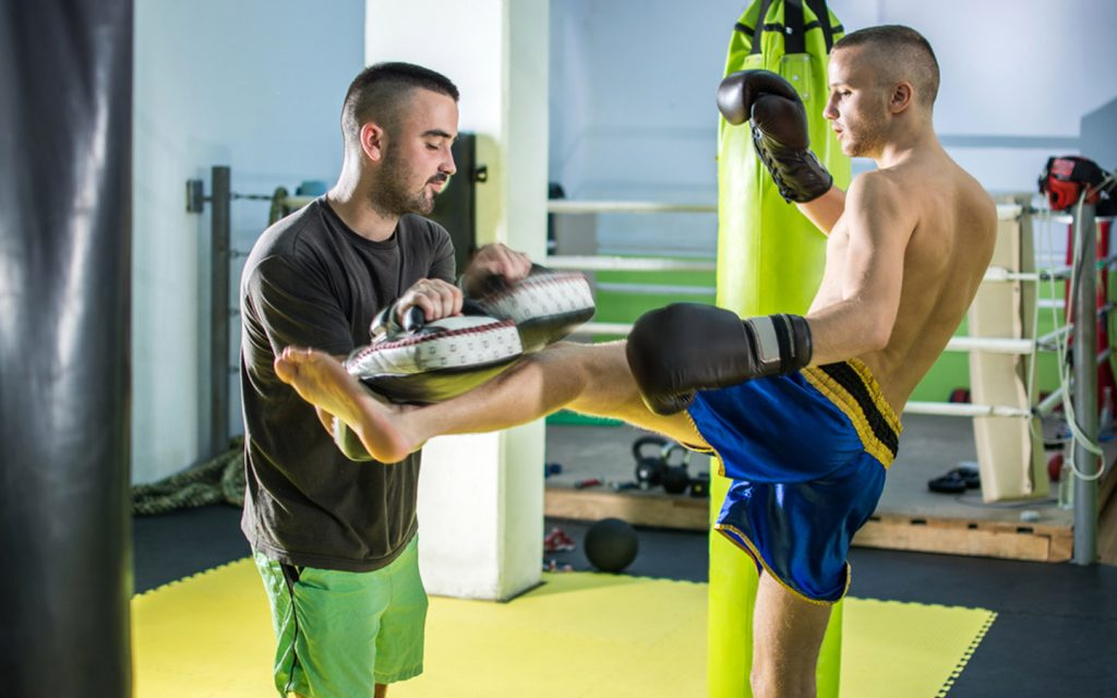 Kickboxer training by kicking trainer