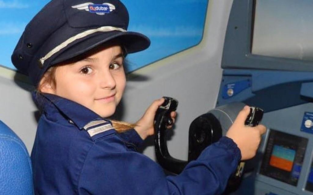 kid operating a flight simulator at KidZania Dubai