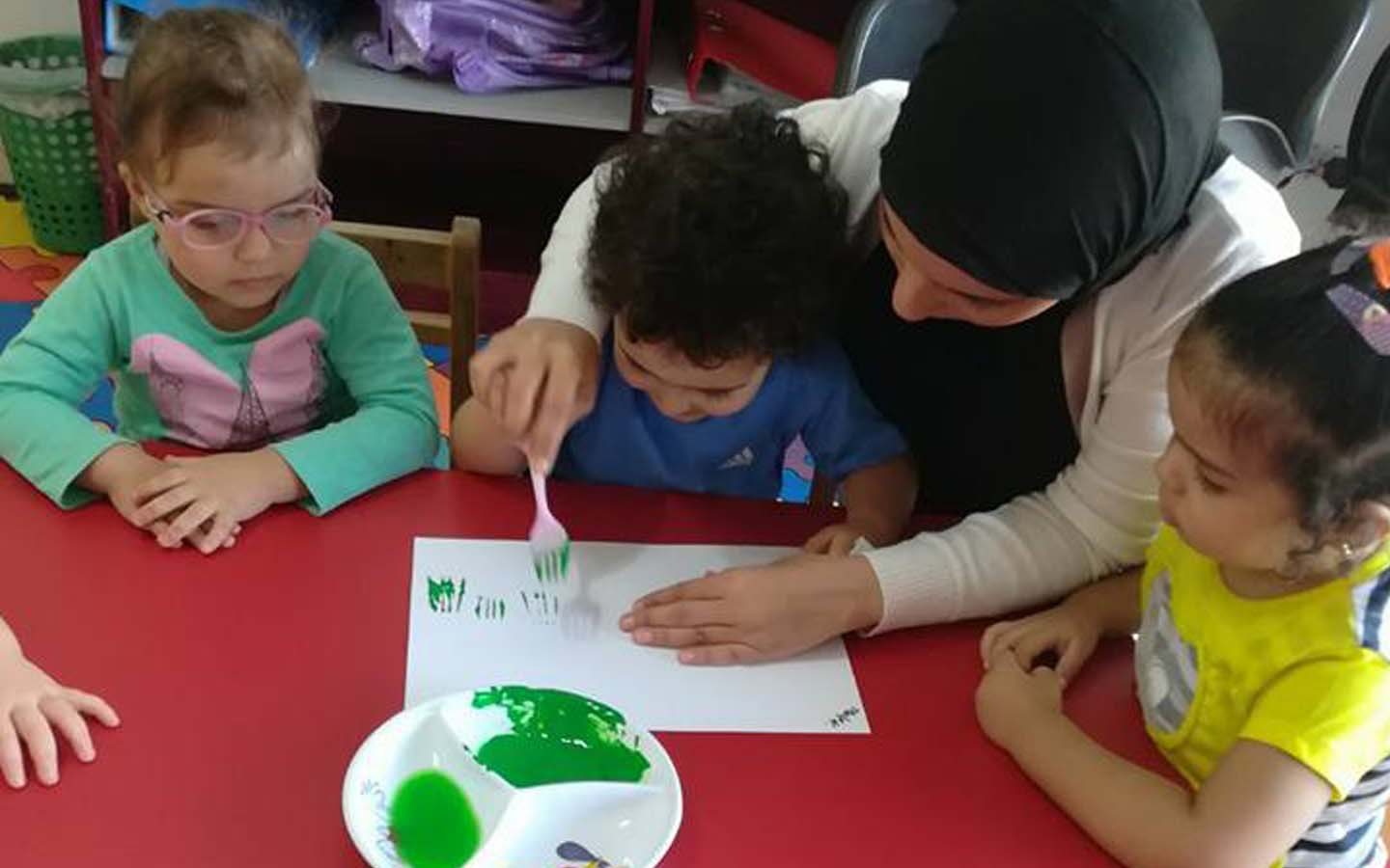 Teacher helping a student in painting at Kids World Nursery