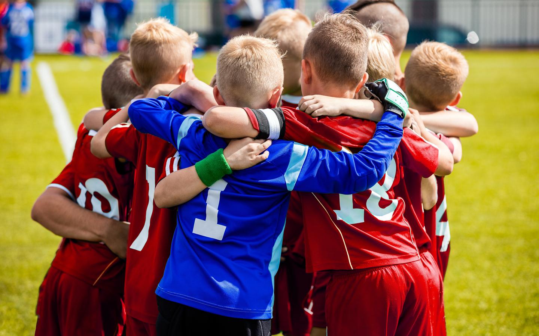 Kids football team huddling