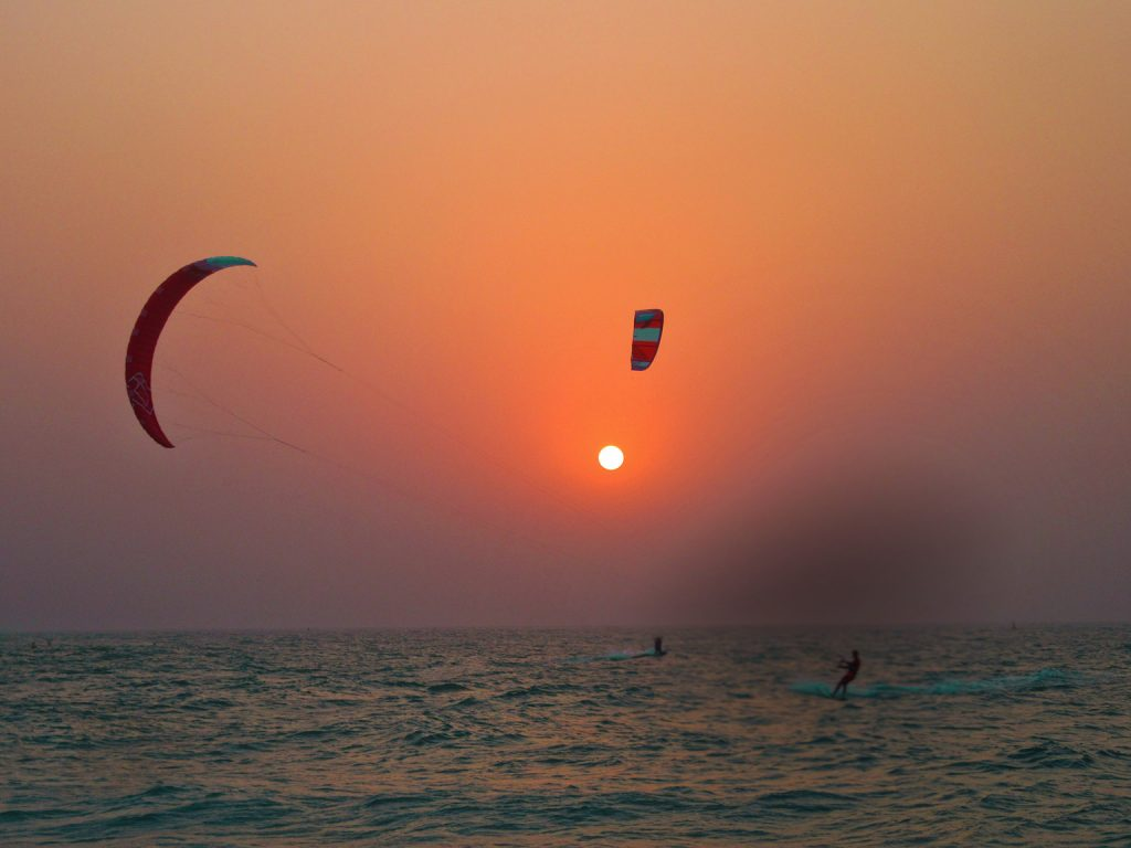 The waters of Arabian Gulf next to Kite Beach, Dubai at sunset with two kite surfers mid surf