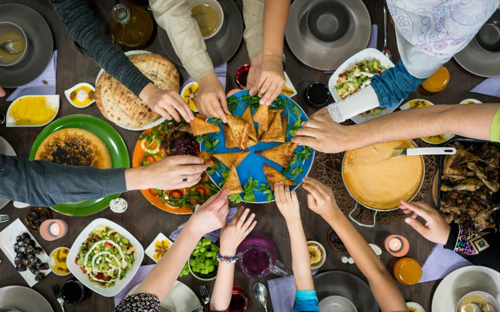 Hands reaching towards a plate of food on the table