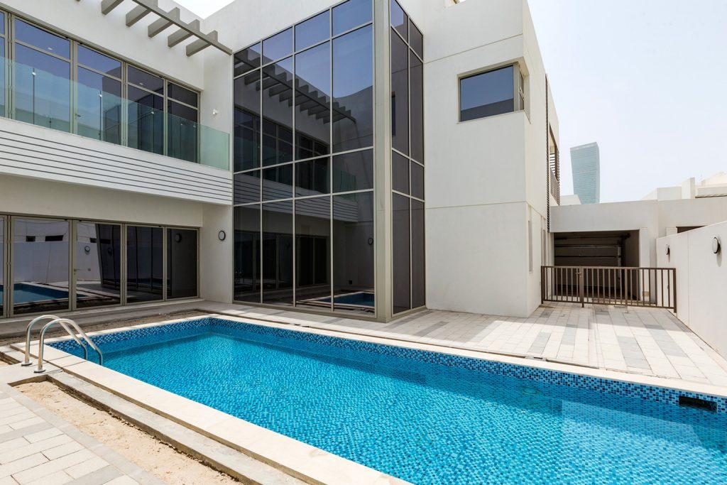 The backside of a beautiful minimalist villa with a long pool in Mohammed Bin Rashid Al Maktoum City Dubai