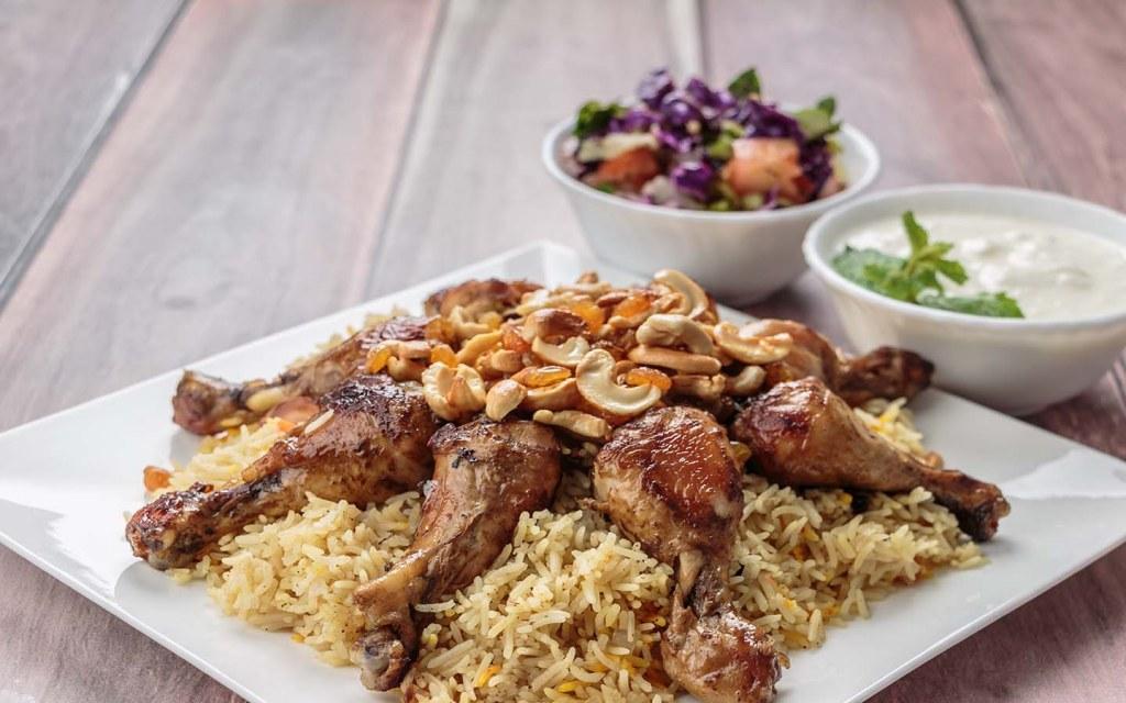 A traditional Chicken Mandi platter served with yogurt and salad.