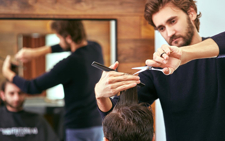 A man's hair cut in progress at a Dubai salon