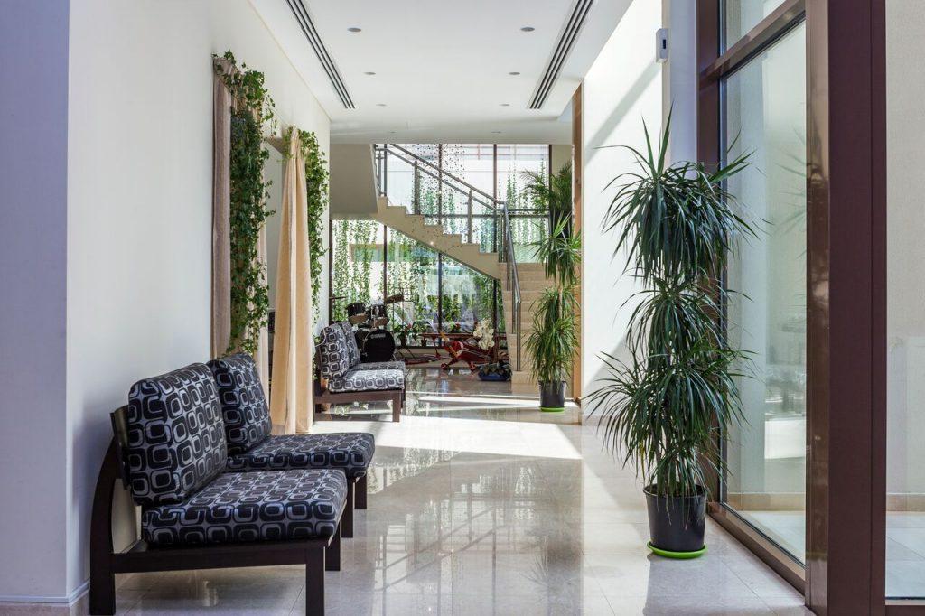 A bright corridor with Arabic-style furniture and plants in a modern villa in Millennium Estates, MBR City Dubai