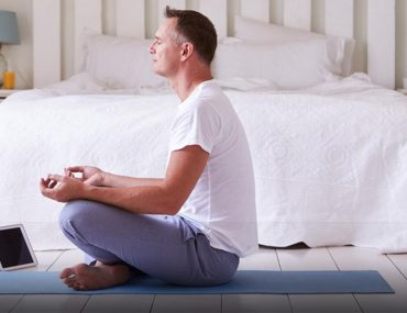 Man meditating on bedroom floor with legs crossed and laptop in front of him