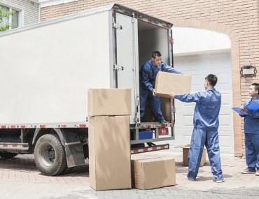 Handy providing Home moving service in Dubai while happy couple looks at them