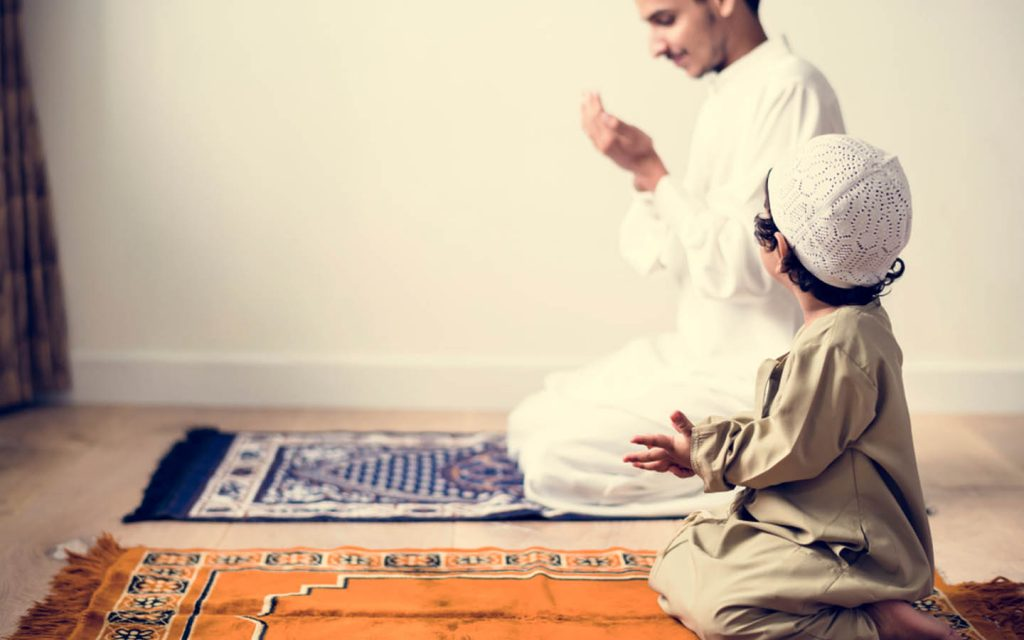 Muslim child praying with his father