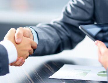 Man shaking hands after signing agreement at National Bonds UAE