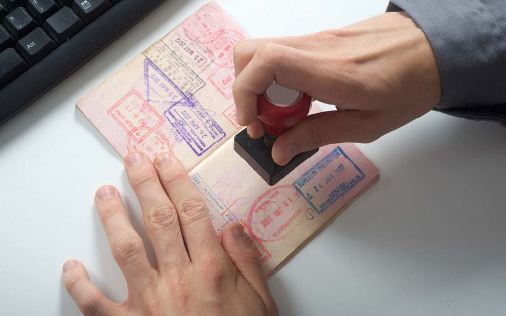 Passport being stamped on a table, after the UAE visa extension update