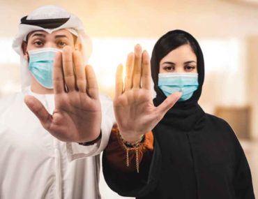 Emirati man and woman in masks
