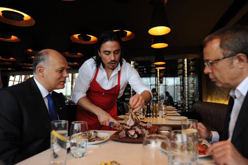 Nusr-Et aka Salt Bae serving steak to visitors in his signature style